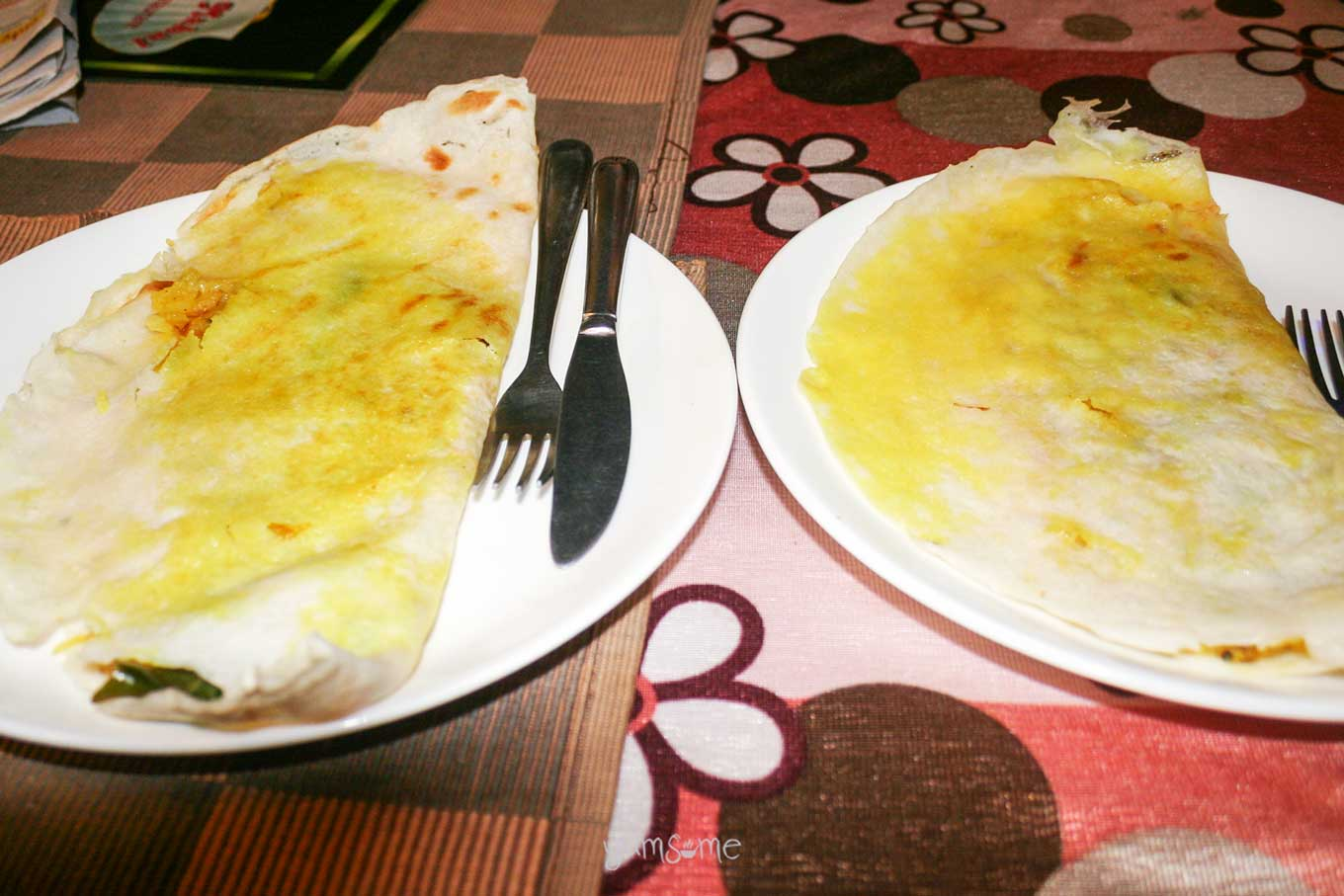 Two masala dosai on white plates, on a coloured tablecloth.