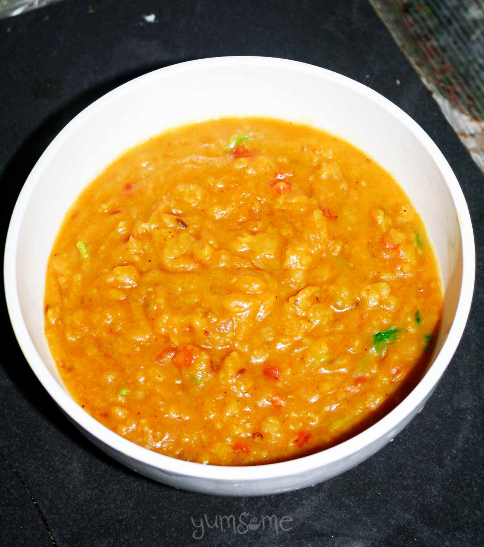 A white bowl containing sambar.