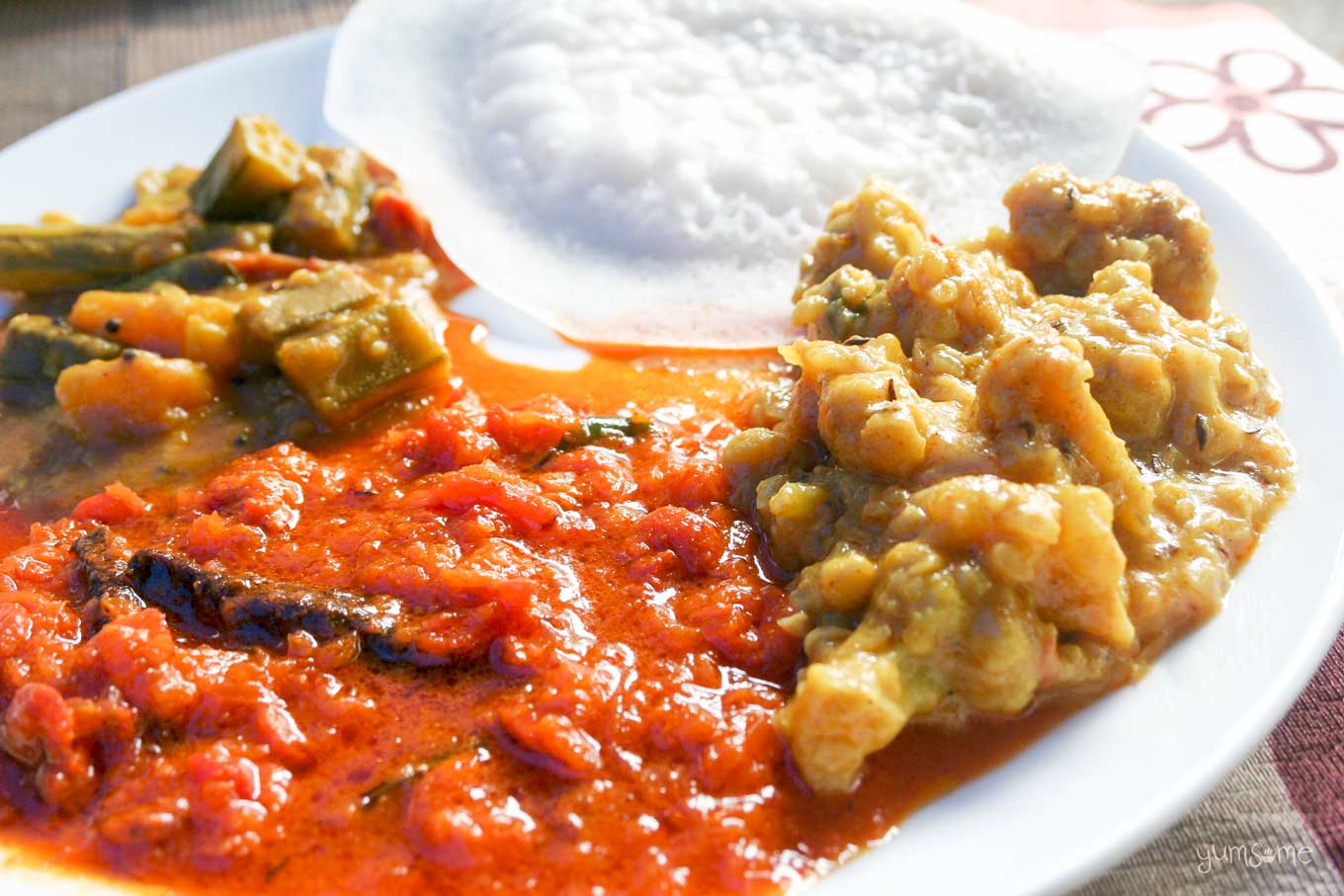 Three vegetarian curries and an appam on a white plate.