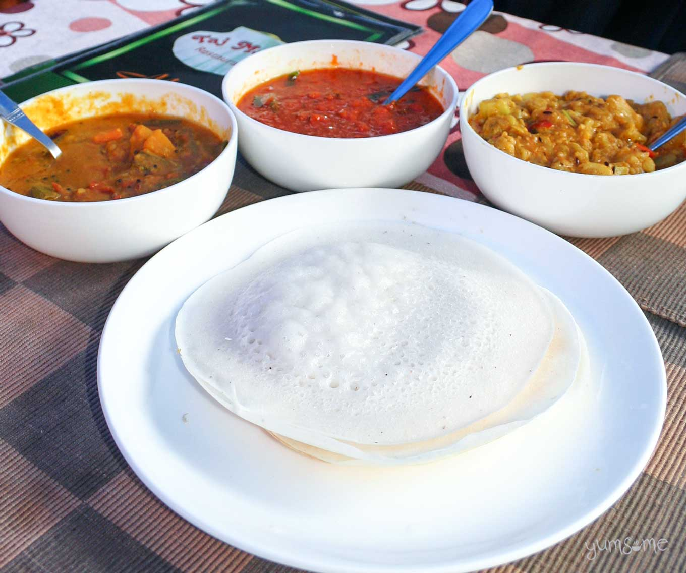 A white plate containing two appams, with three bowls of vegetarian curries behind it.