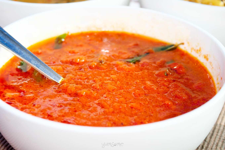 A white bowl containing vibrant orangey-red tomato masala.