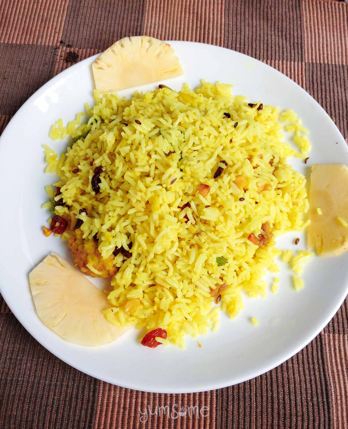 A white plate of vegetable biryani on a coloured background.