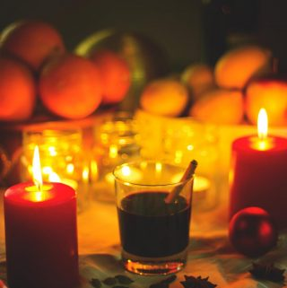 Candlelit glasses of mulled wine, with seasonal fruits in the background.