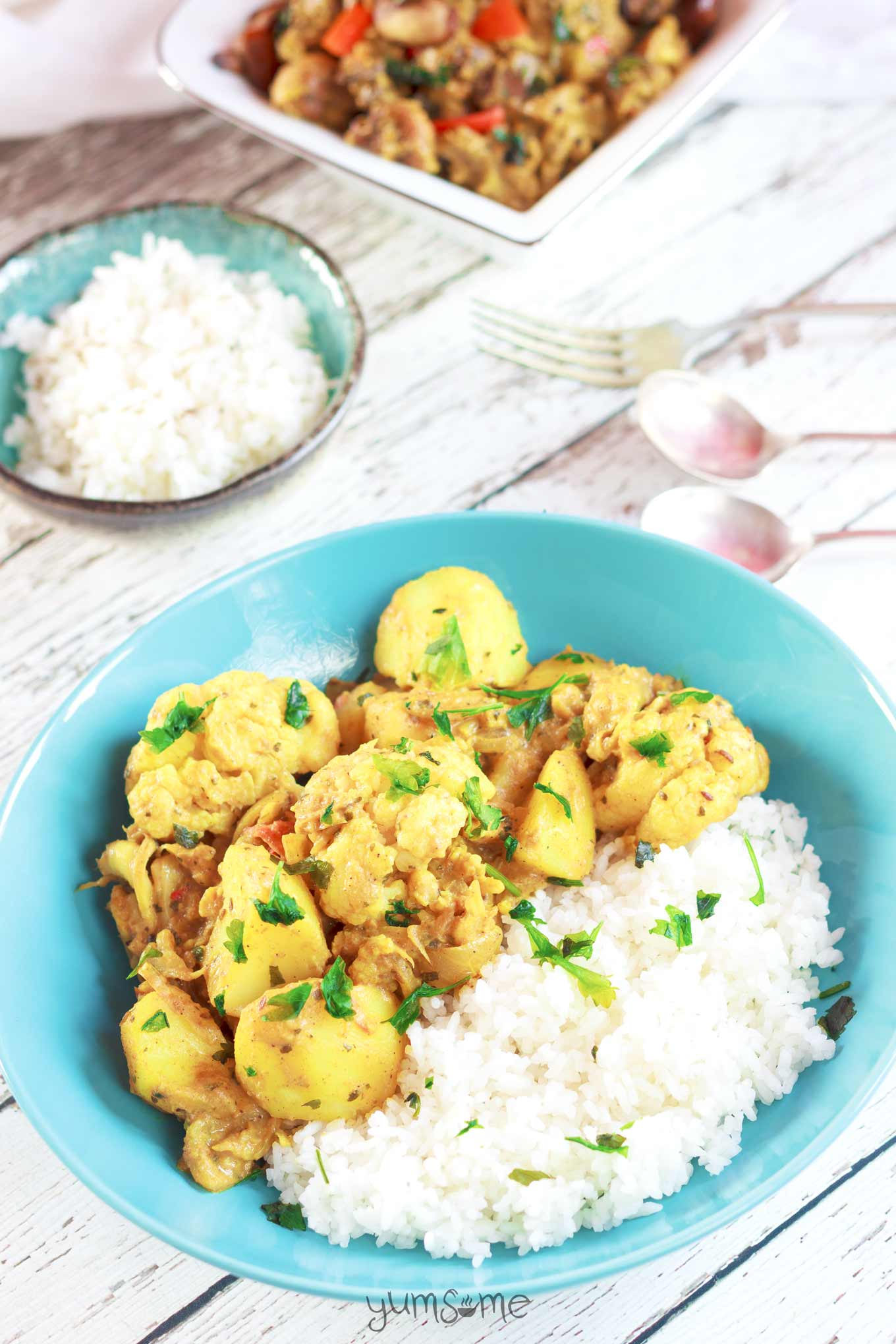 A bright blue bowl containing rice and simple vegan aloo gobi masala.