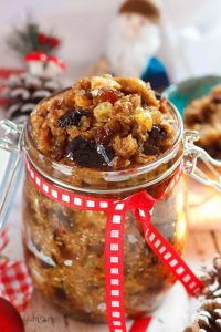 A jar of vegan mincemeat, with Christmas decorations in the background.
