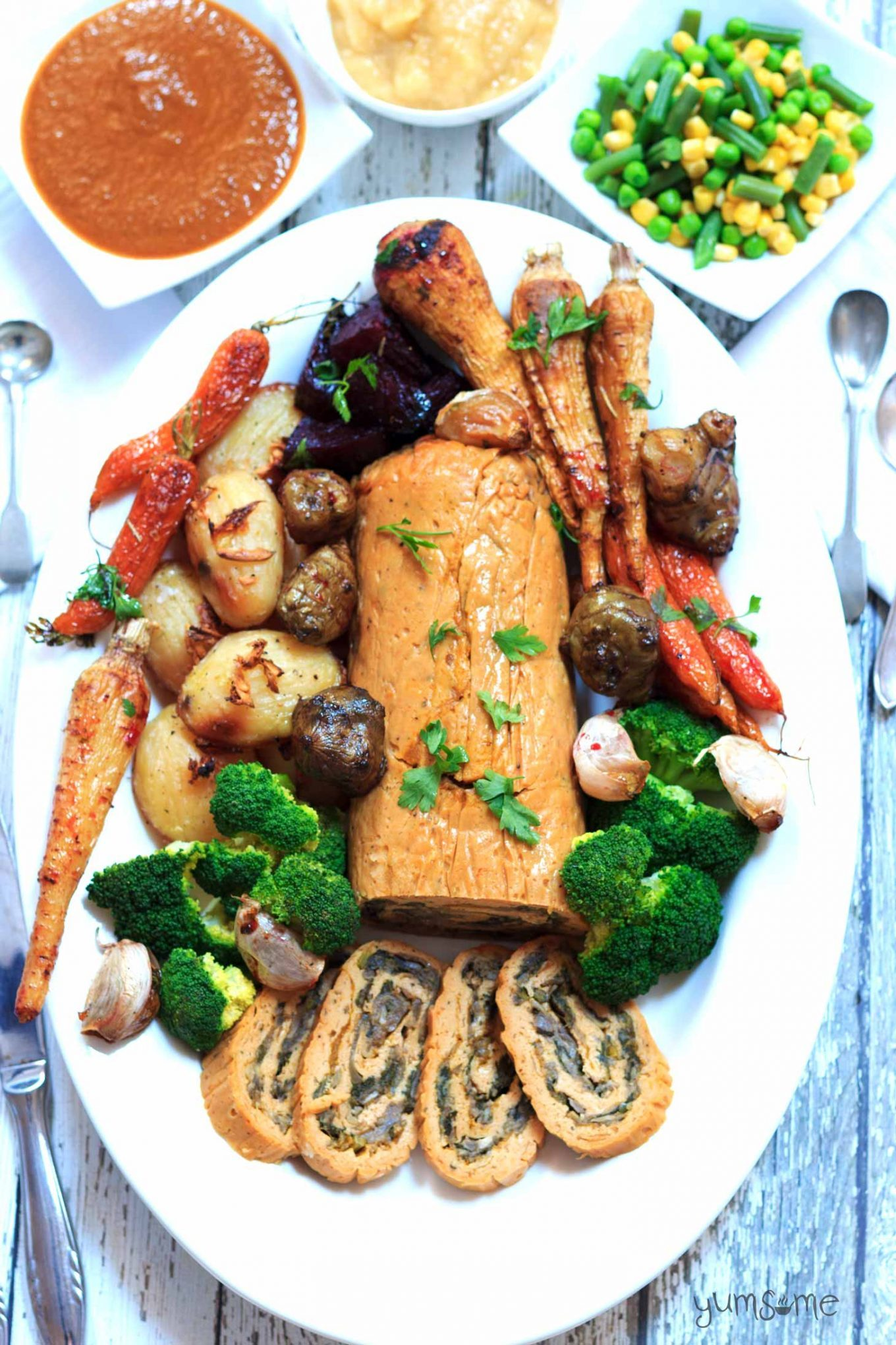 Overhead shot of a stuffed seitan roast on a platter, surrounded by roasted vegetables. Gravy, mashed potato, and steamed green beans are in white dishes in the background.