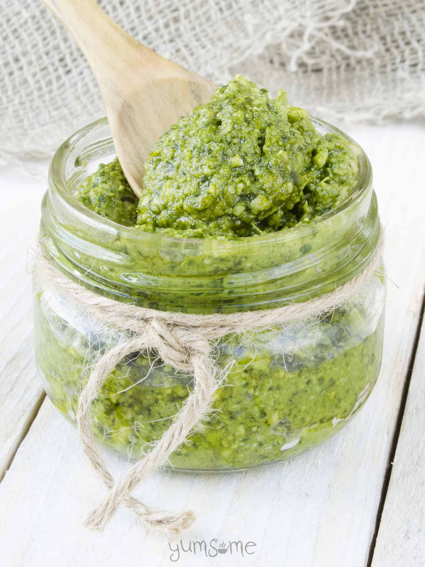 A jar of 5-minute vegan cashew pesto, with a wooden spoon in it.