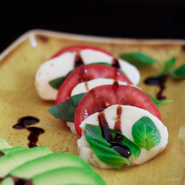 Vegan caprese il tricolore with avocado on a yellow plate.