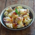 A black and white bowl of vegan potato salad, with paprika and a sprig of tarragon.