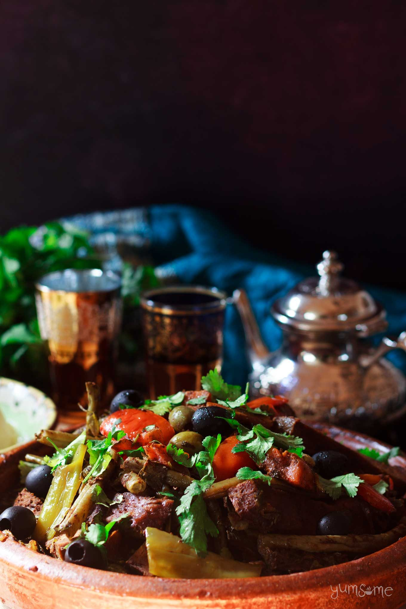 Moroccan vegetable tagine with a pot of tea and two glasses.