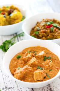 A bowl of vegan paneer butter masala on a white table, with bowls of vegan dal fry and aloo masala in the background.