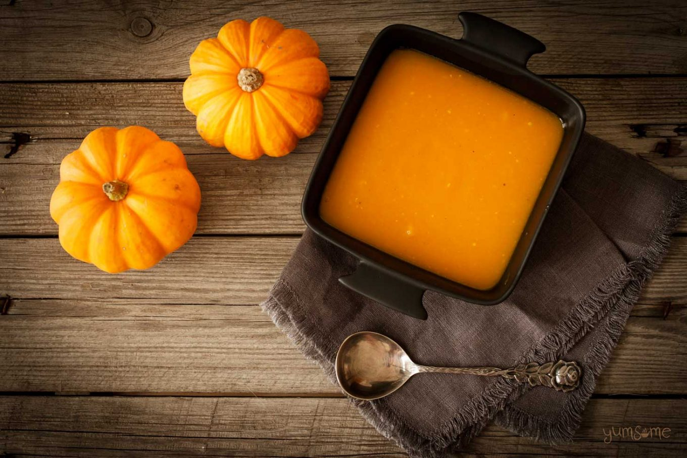 Two pumpkins and a bowl of pumpkin soup on a wooden table.