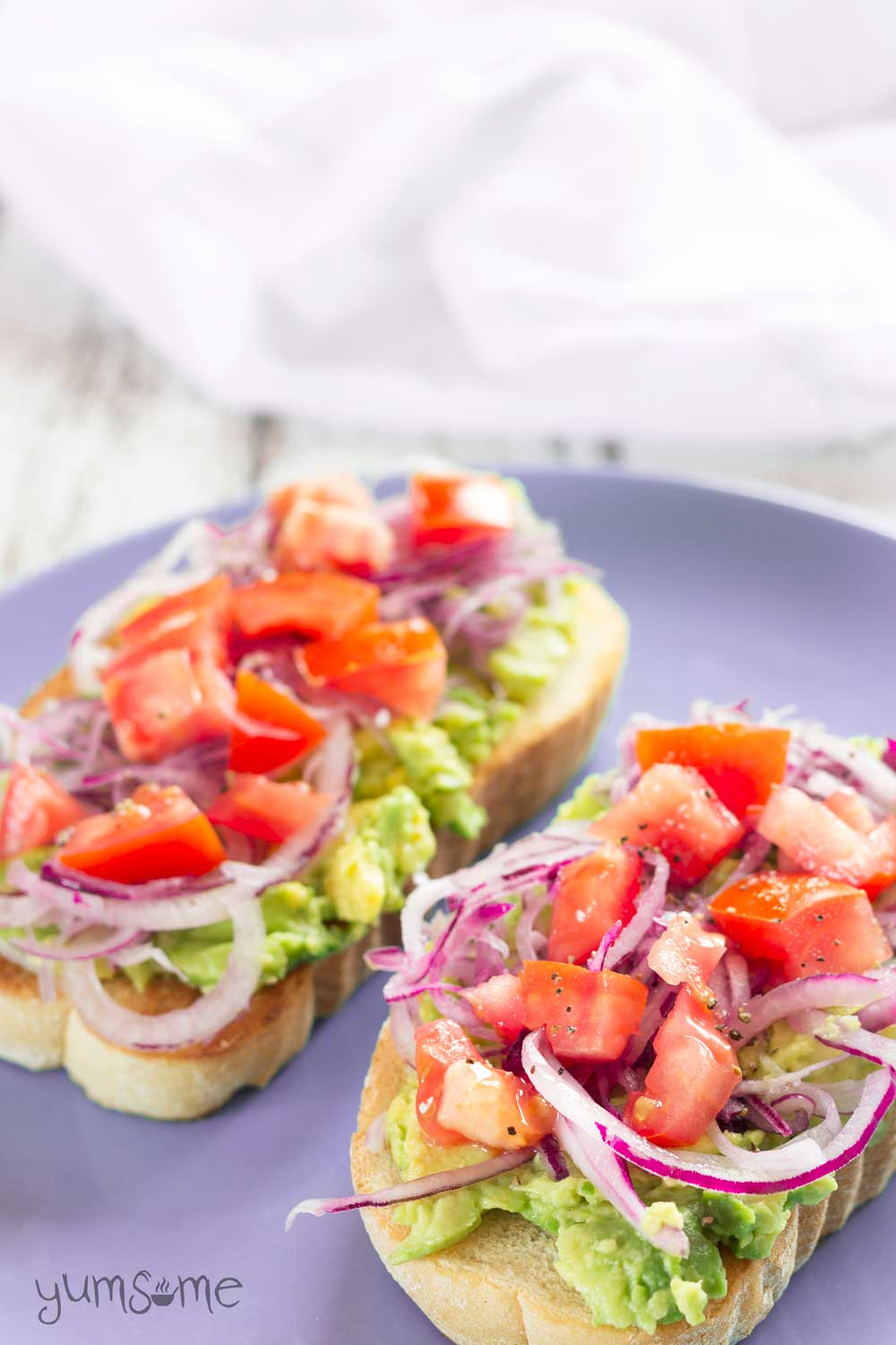 a lilac plate with avocado and tomato bruschetta | yumsome.com