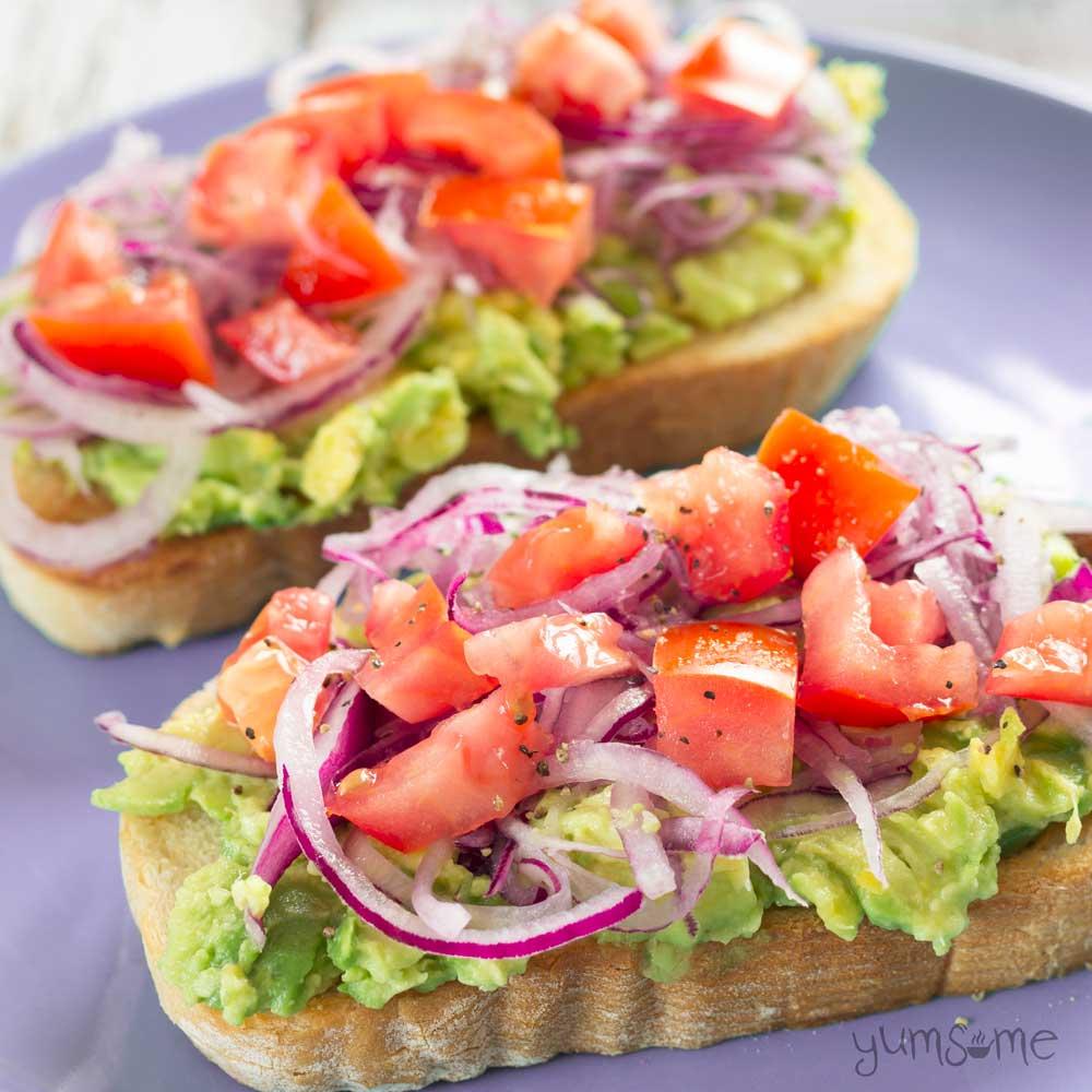 closeup of two slices of avocado and tomato bruschetta | yumsome.com