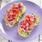 Avocado and tomato bruschetta on a lilac plate.