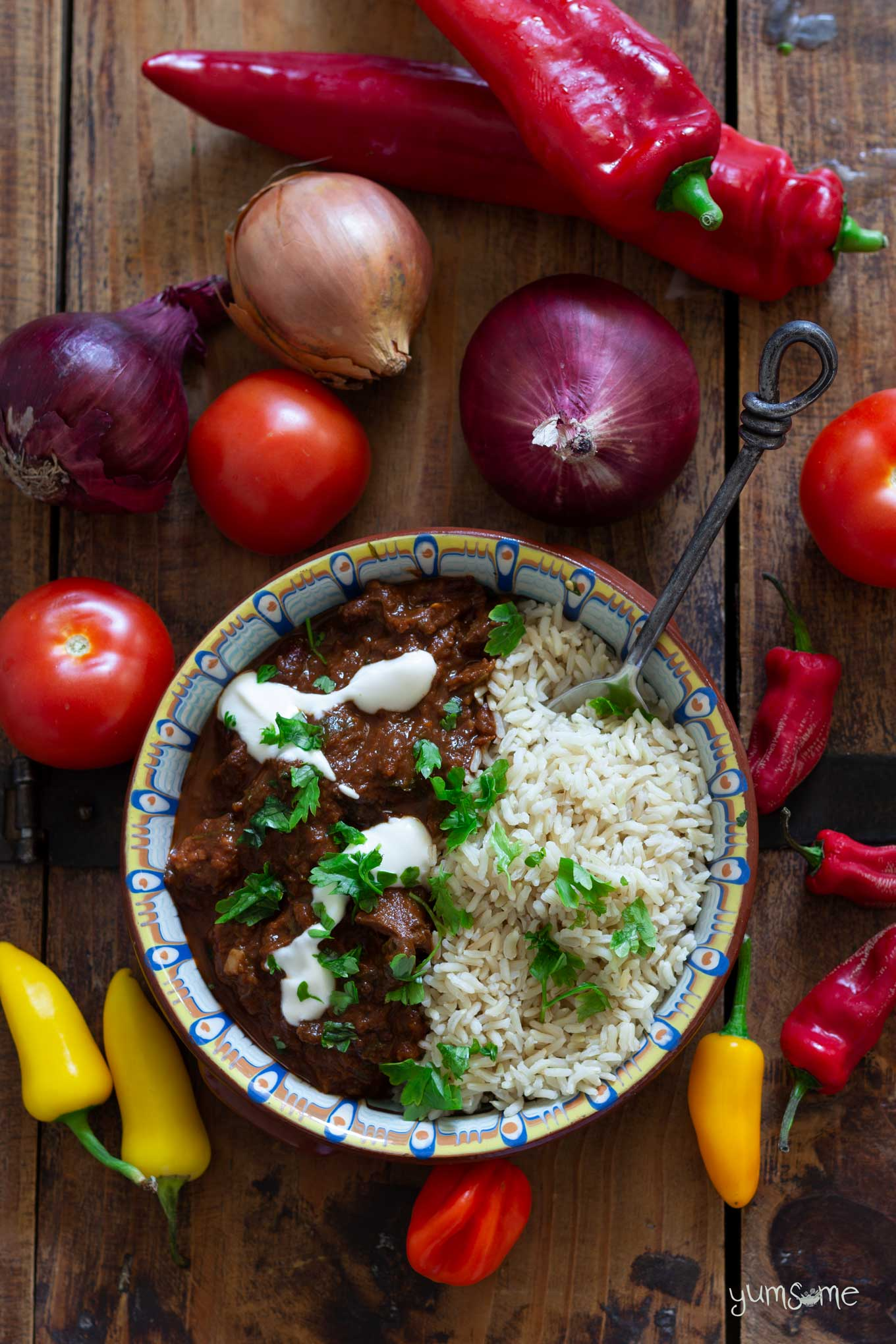 A bowl of chocolate chilli and rice on a wooden table with an assortment of vegetables.