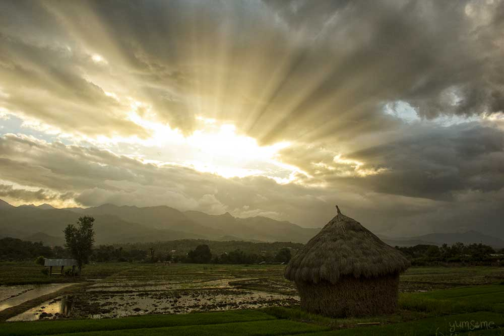 Sunset over a haystack in a field at Mae Hee, Thailand.