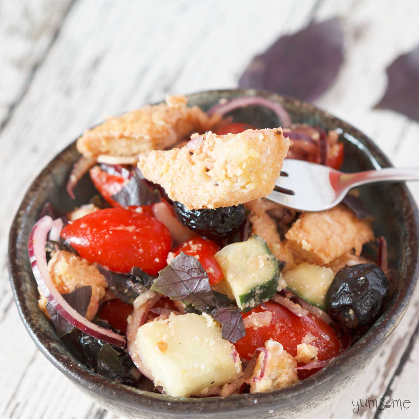 A bowl of vegan panzanella with a fork holding a piece of bread.