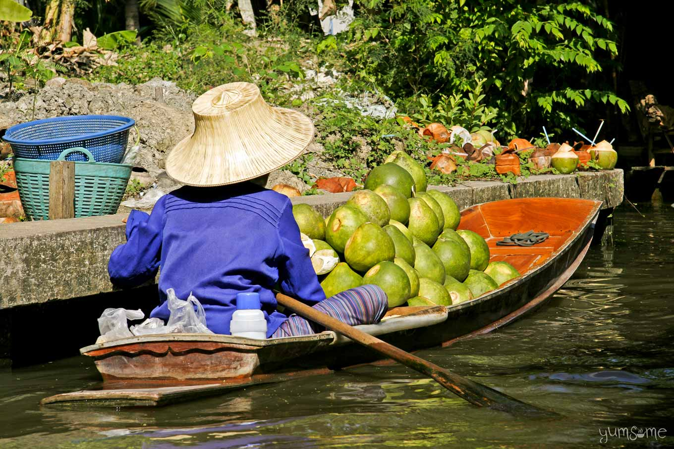 A trader selling pomelos in their boat at a floating market in Thailand.