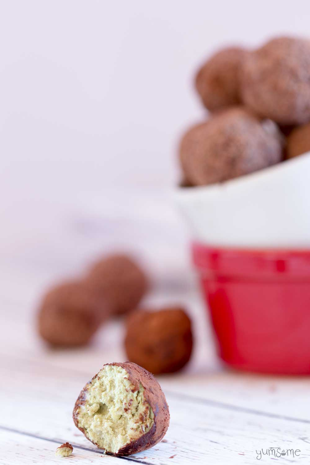A cut open vegan chocolate matcha truffle on a white table, with more truffles in the background in red and white dish.