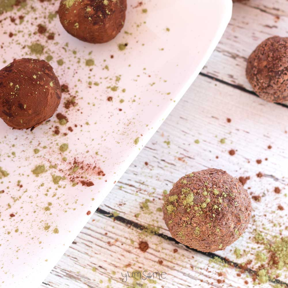 Vegan chocolate matcha truffles on a white table, with cocoa and matcha scattered around.