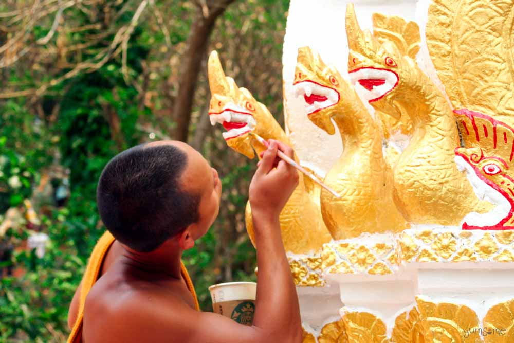 A Buddhist monk repairs a Naga statue at Wat Doi Suthep, Chiang Mai.