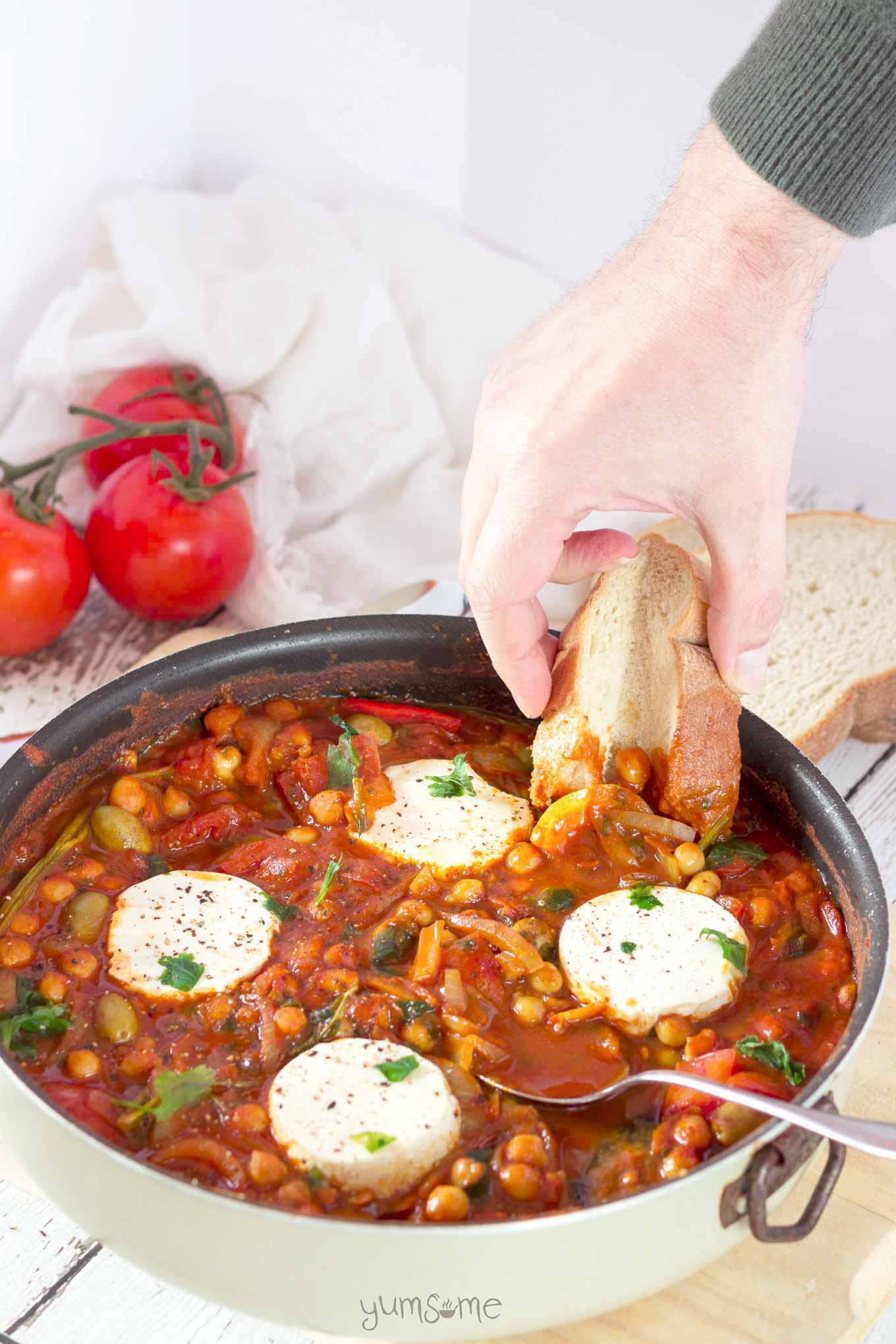 A hand dipping some bread into a pan of vegan shakshuka.