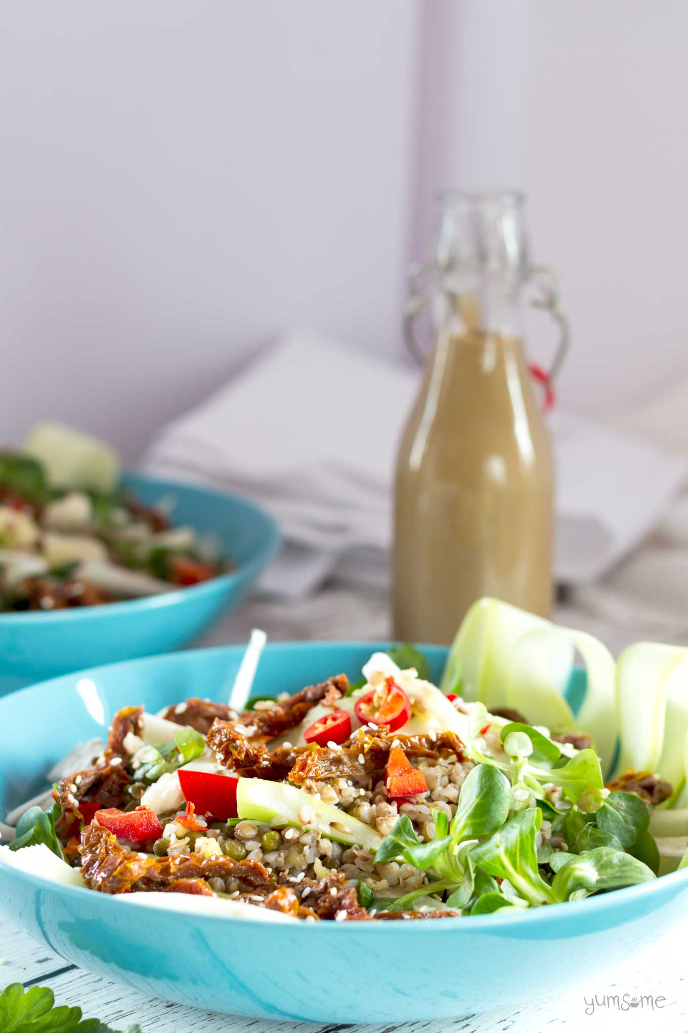 two blue bowls of spicy buckwheat and mungbean salad on a table with a bottle of tahini dressing | yumsome.com