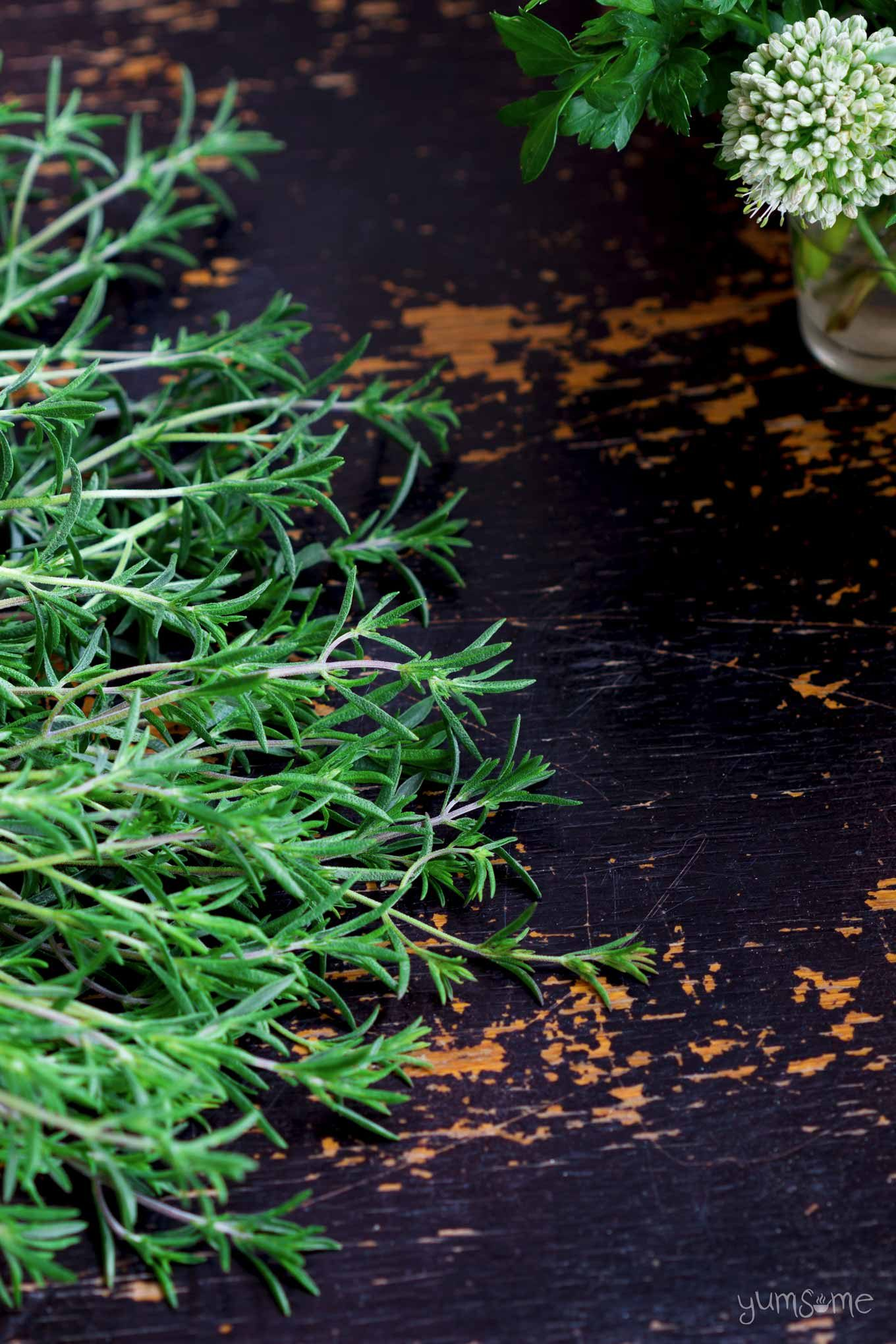 Fresh savory with other herbs on a black table.