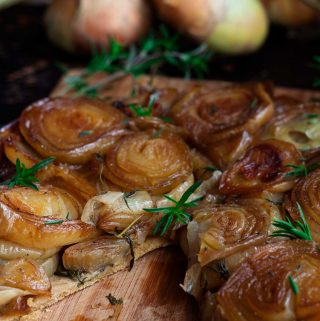 Closeup of caramelized onion tarte tatin on a wooden board, with a slice removed.