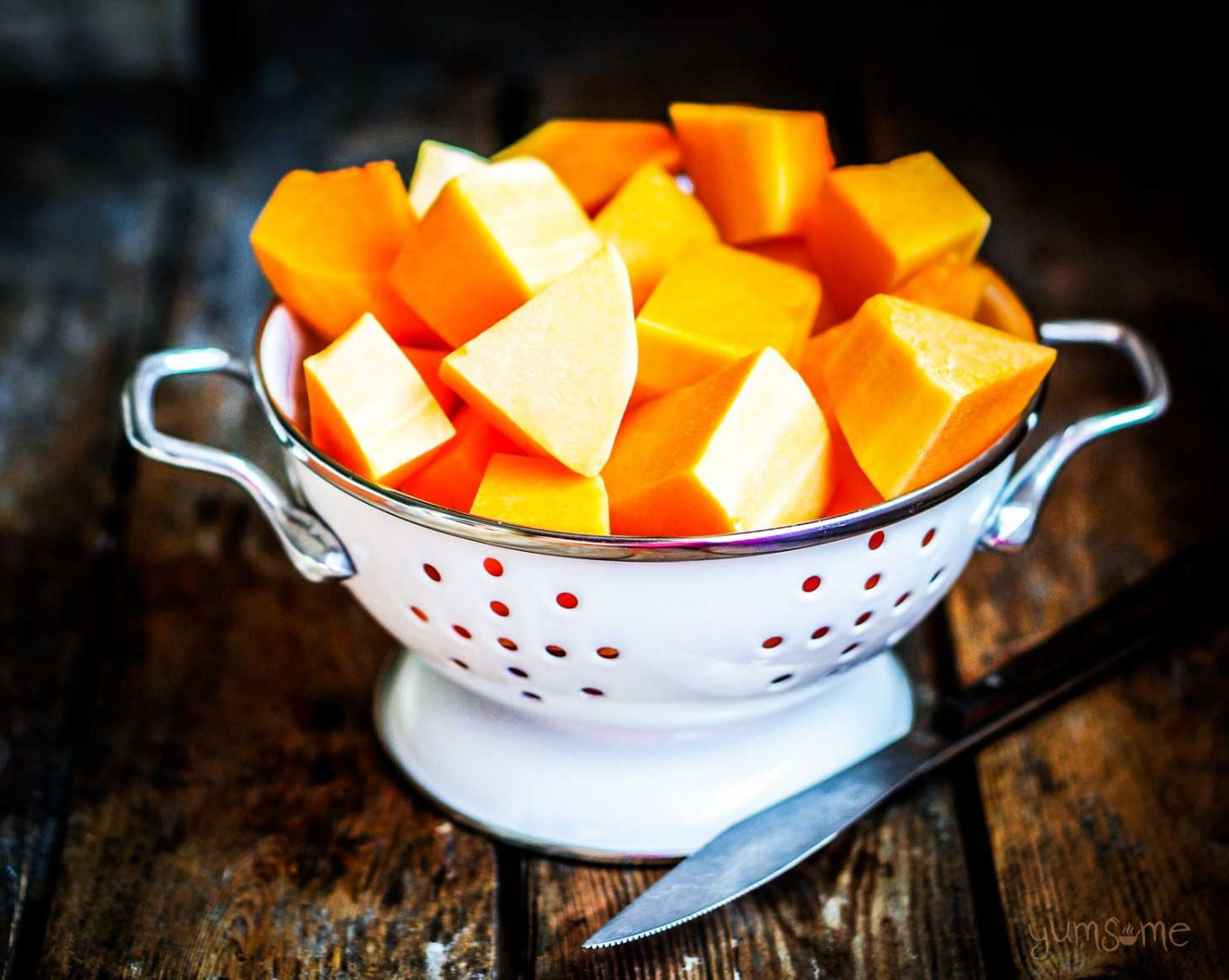 A white colander filled with diced pumpkin, on a dark wooden table.