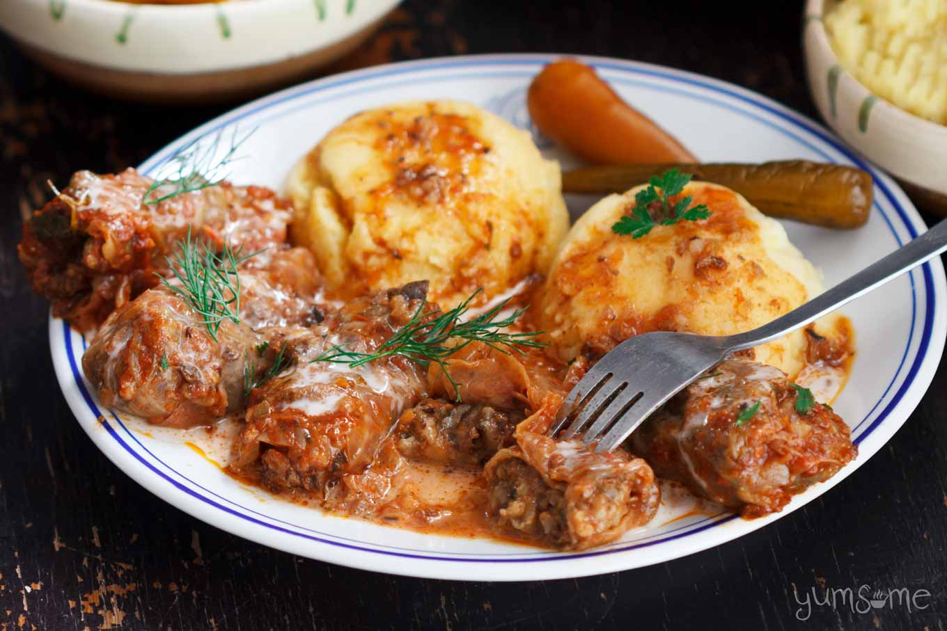 a plate of romanian cabbage rolls with mashed potatoes and mamaliga | yumsome.com