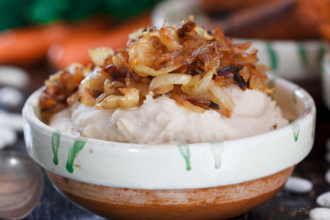 An earthenware bowl of fasole bătută, topped with caramelised onions.