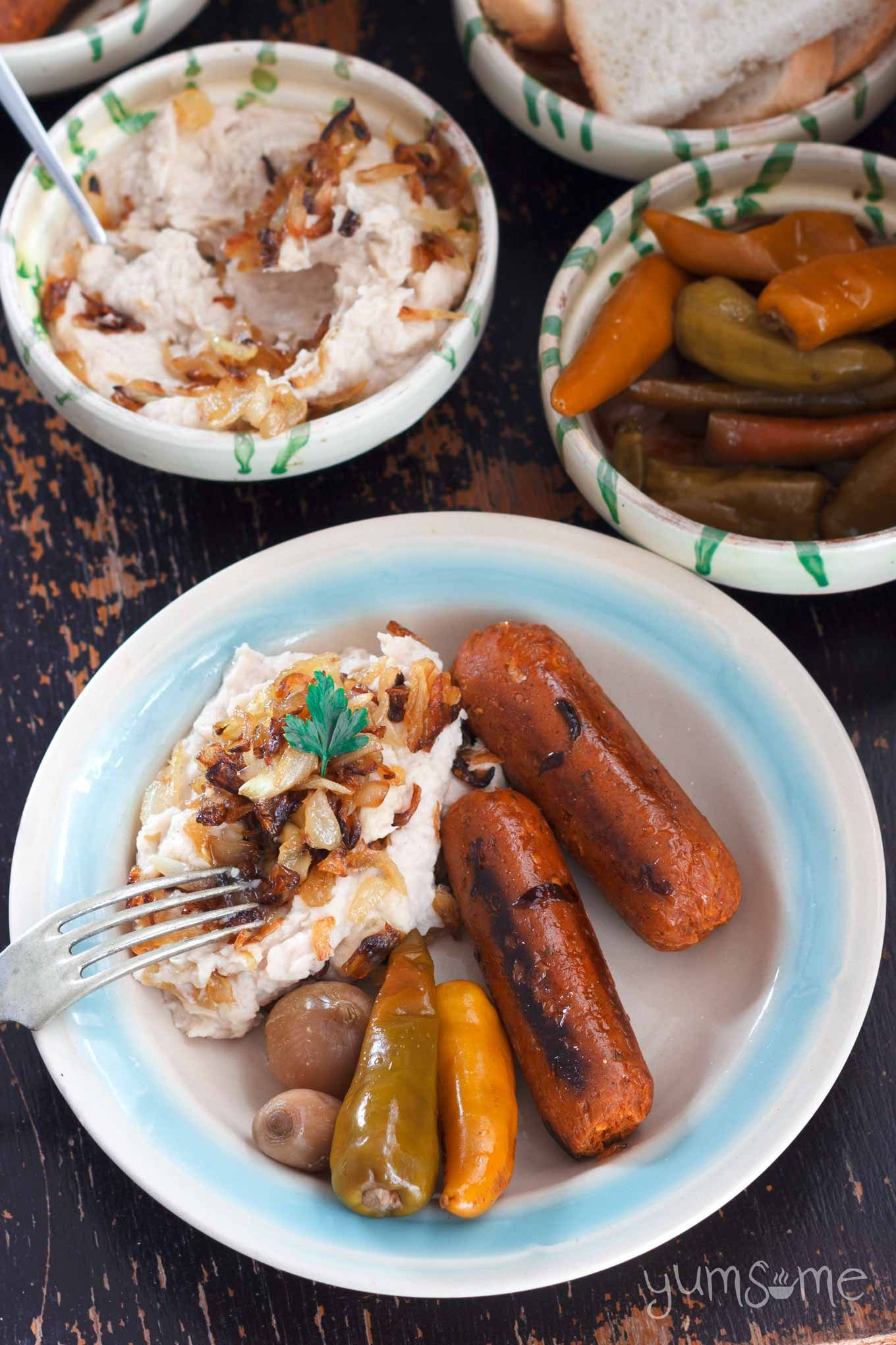 Closeup overhead shot of a blue and white dish of fasole with caramelised onions, sausages, and pickles. Dishes of fasole and pickles are in the background.