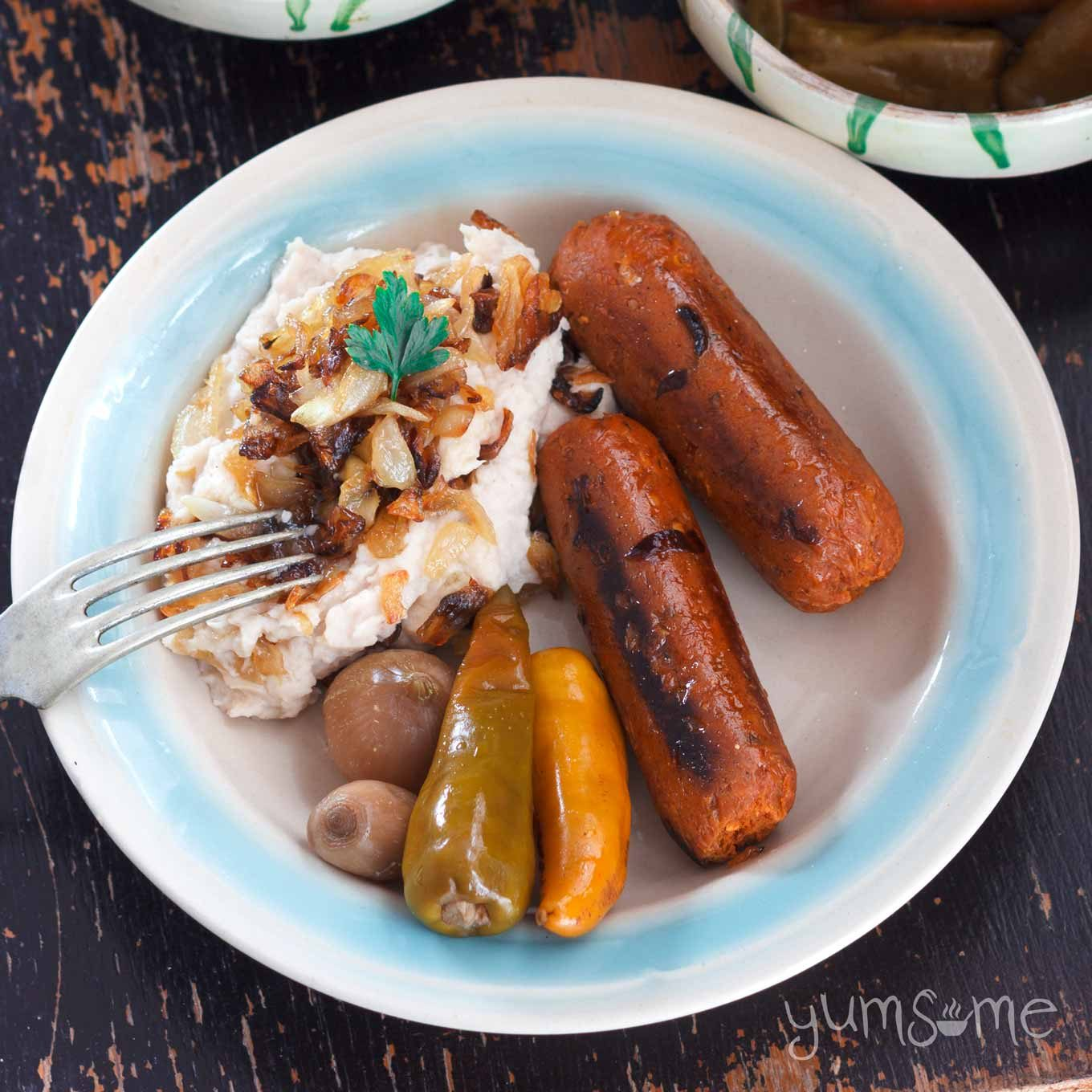 A white and blue plate with fasole bătută, sausages, and various mixed pickles, on a dark table.