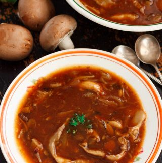 Two dishes of hearty vegan mushroom soup on a black table, with raw chestnut mushrooms and parsley.