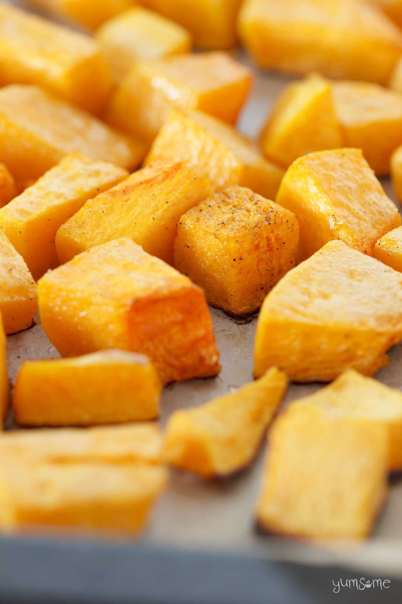 Cubes of cooked pumpkin on a baking tray.
