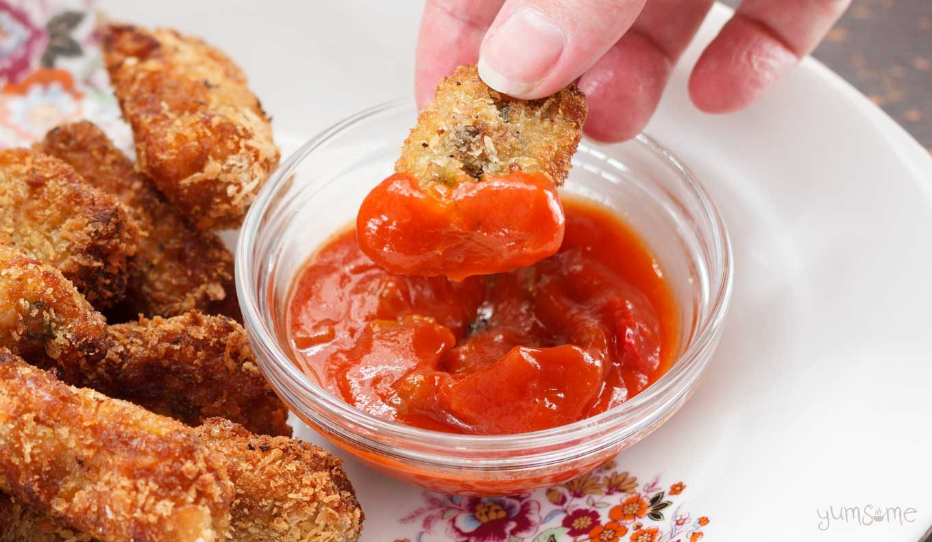 Close-up of cheesy pumpkin tots dipped in salsa.