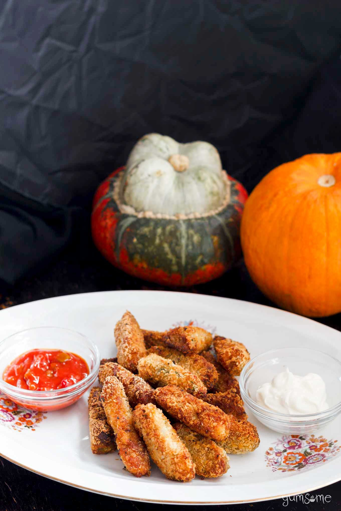 a white plate of vegan baked cheesy pumpkin tots with pumpkins in the background.