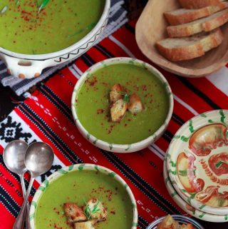 Overhead view of two bowls of piquant pea and leek soup on a red and white cloth, plus a toureen of soup and a basket of sliced bread.