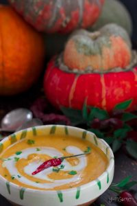 Pumpkins and a bowl of Curried Coconut Butternut Squash Soup against a dark background.