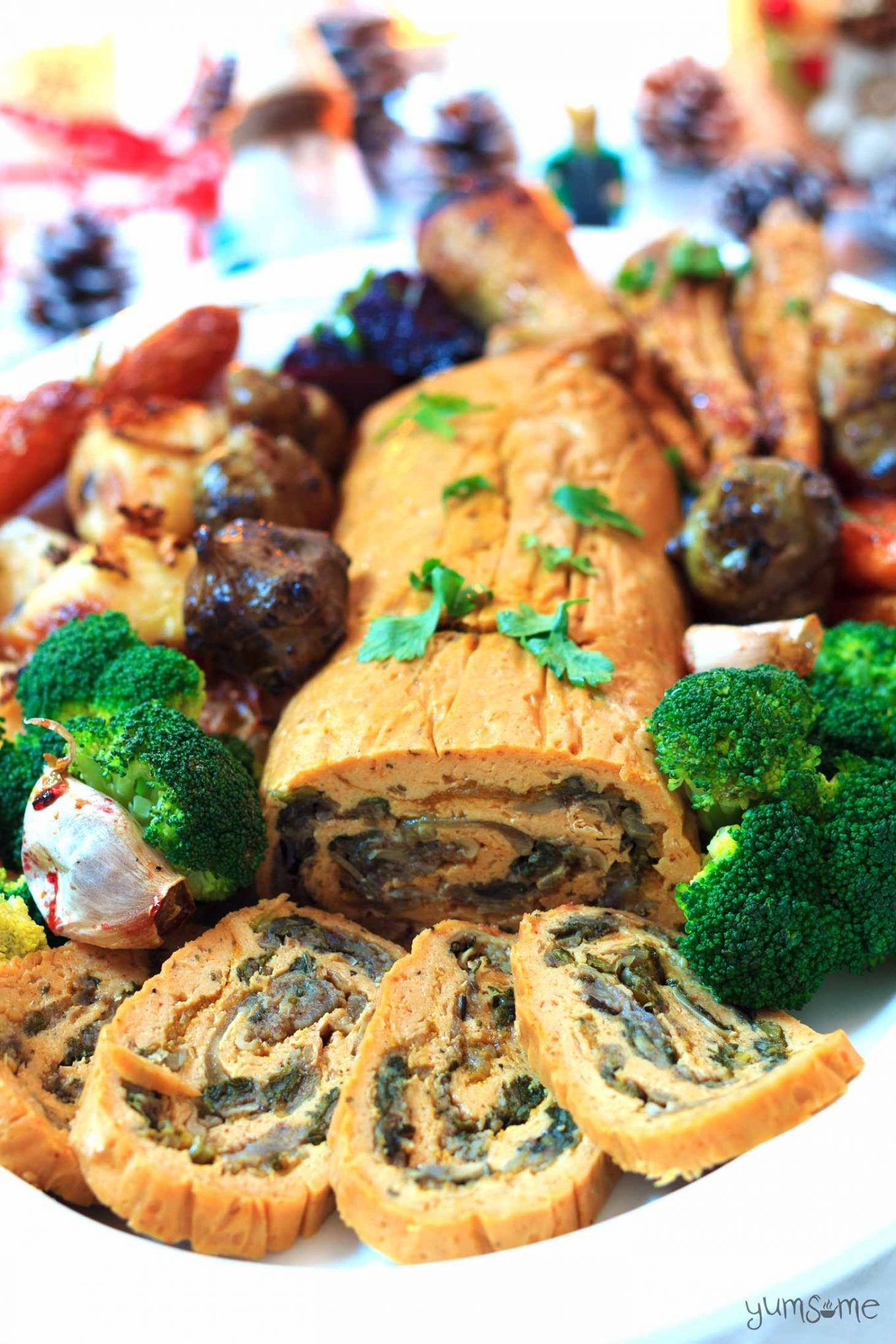 Roast seitan roulade with vegetables on a white platter.