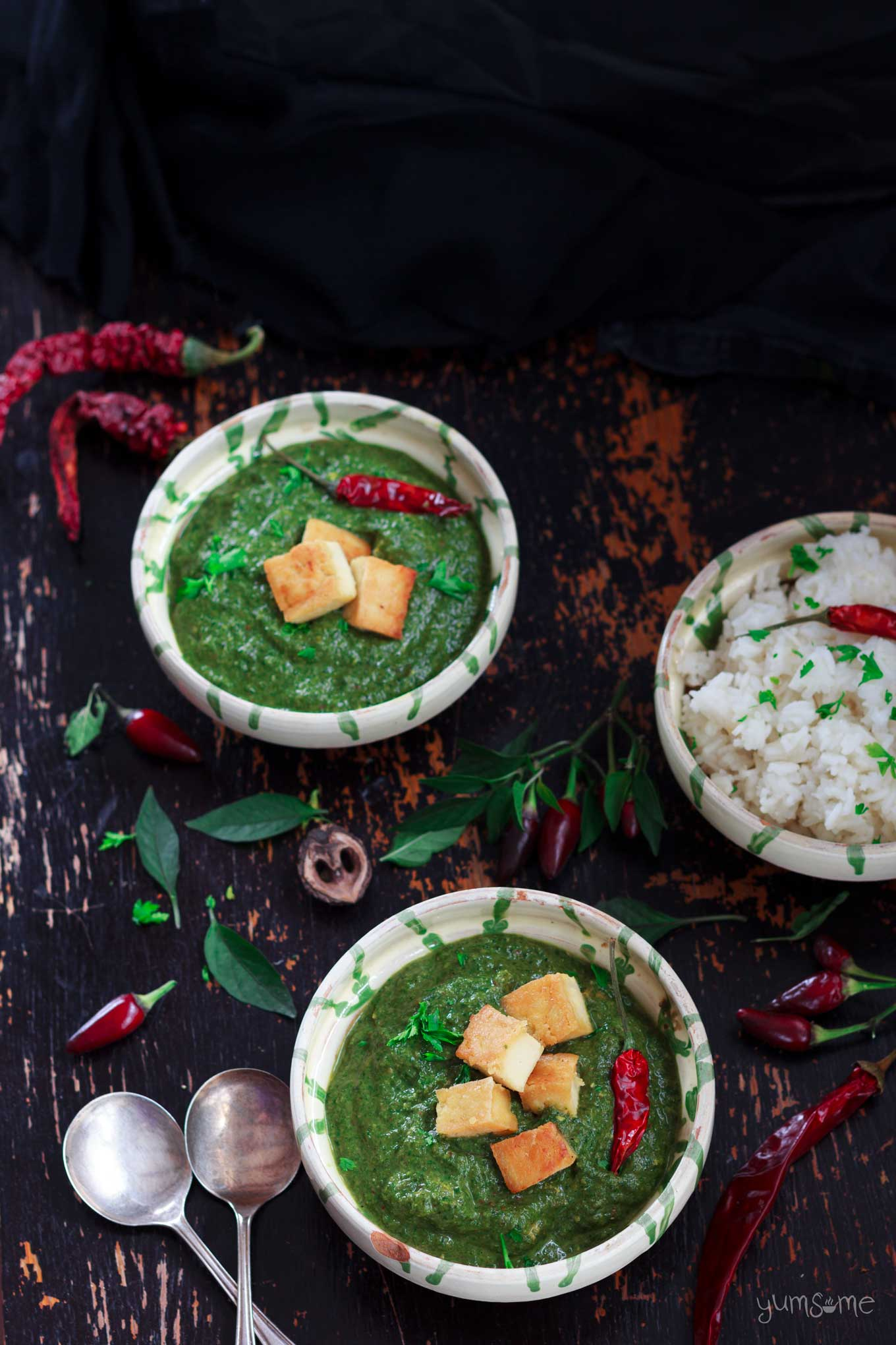 Overhead shot of two bowls of vegan palak paneer and some rice, surrounded by chillies on a dark background.