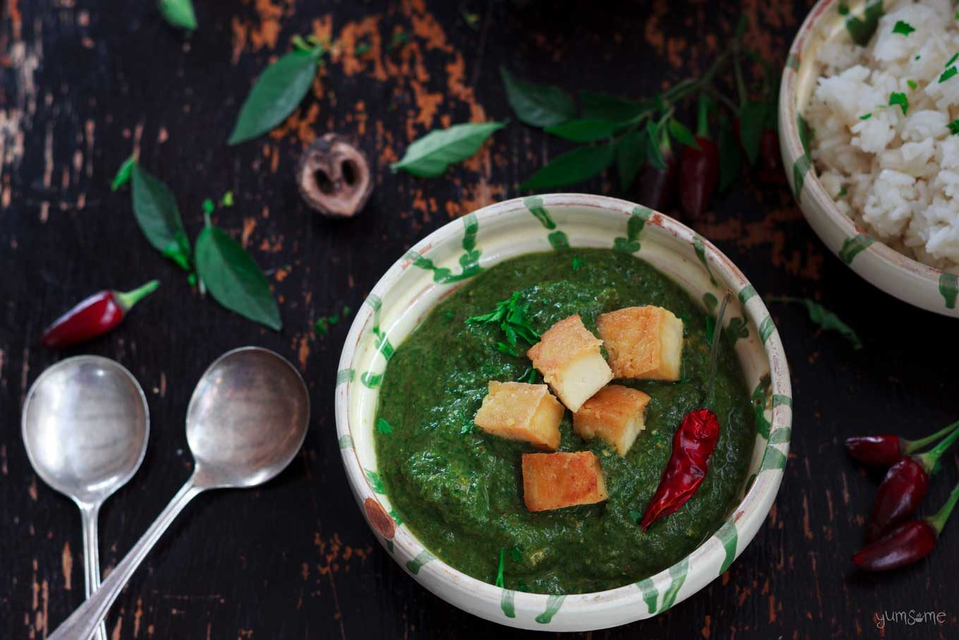 A bowl of vegan palak paneer and two silver spoons on a dark wood table.