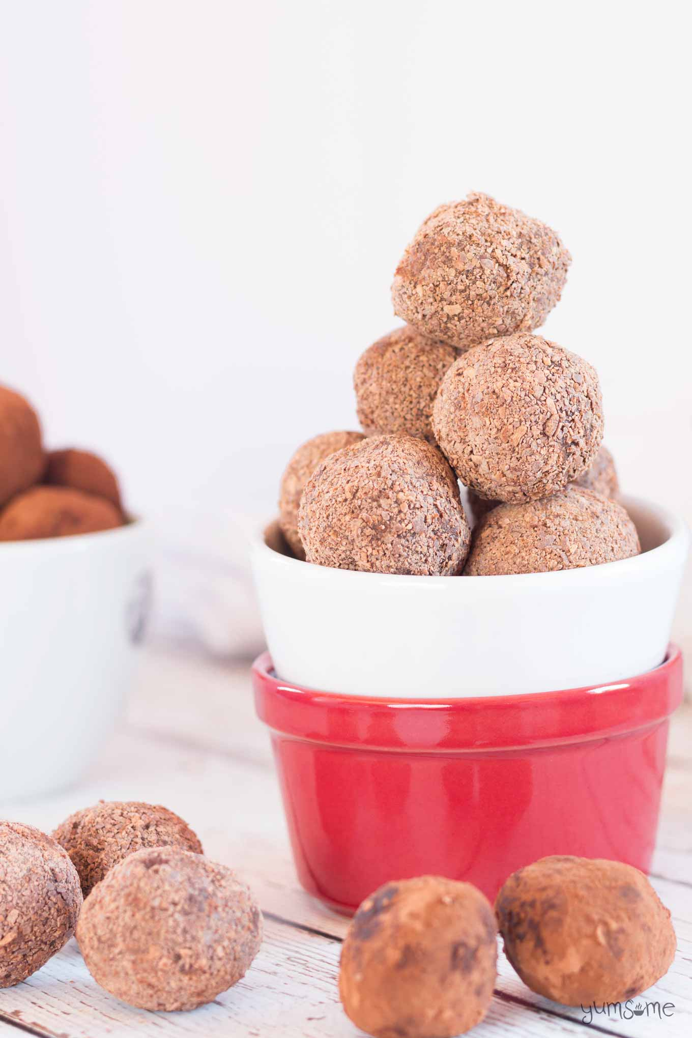 A stack of vegan raspberry chocolate truffles in a red and white bowl.