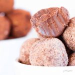 A pile of vegan raspberry chocolate truffles with a bite taken from one.