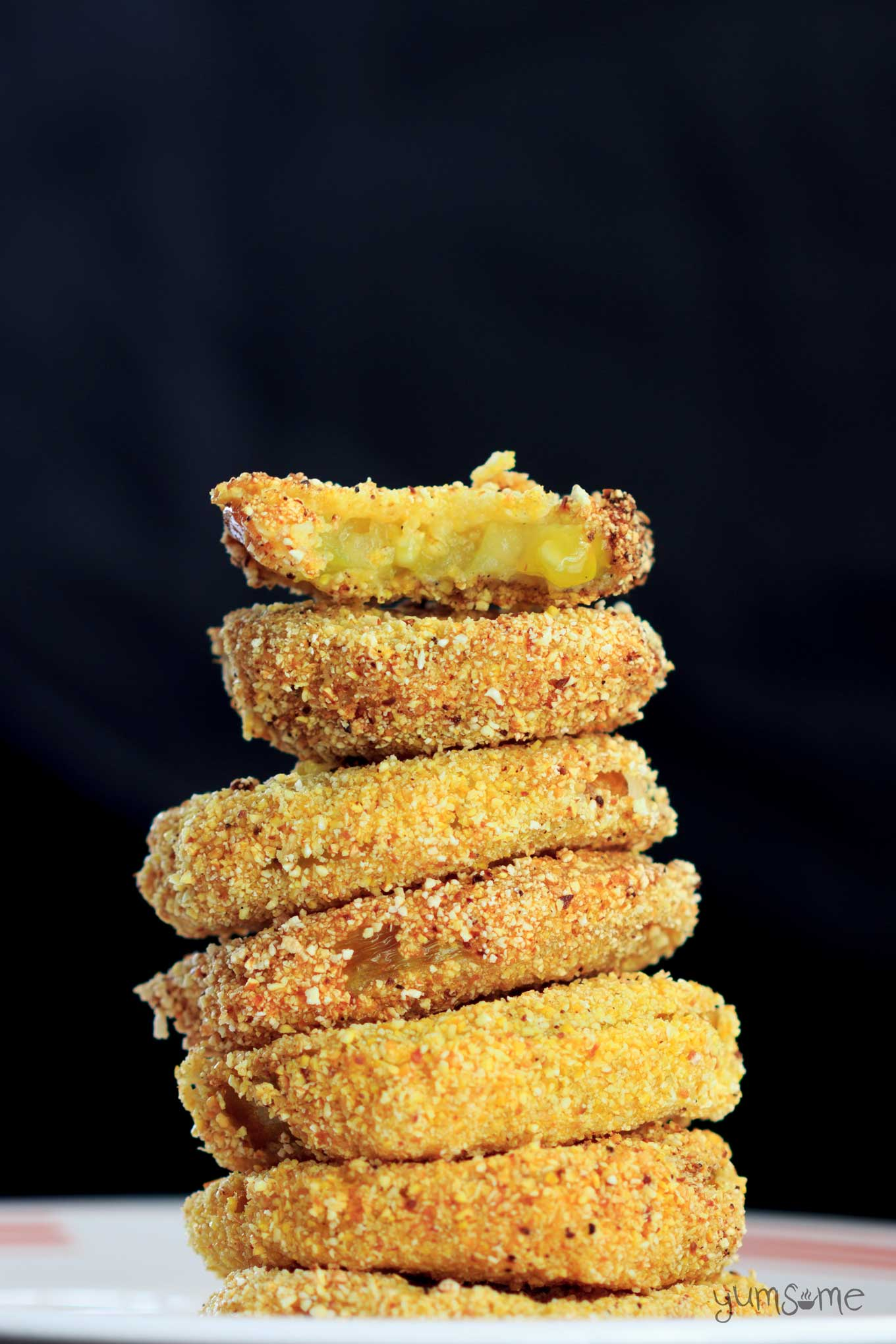 A stack of fried green tomatoes against a dark background.