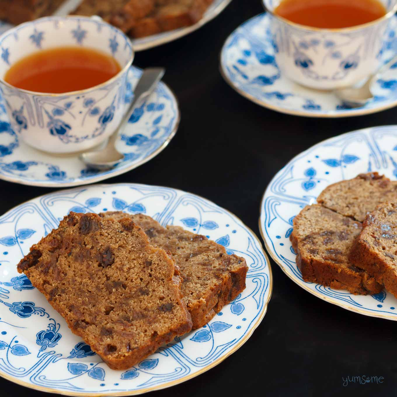 Closeup of two plates of English tea loaf and two cups of tea.