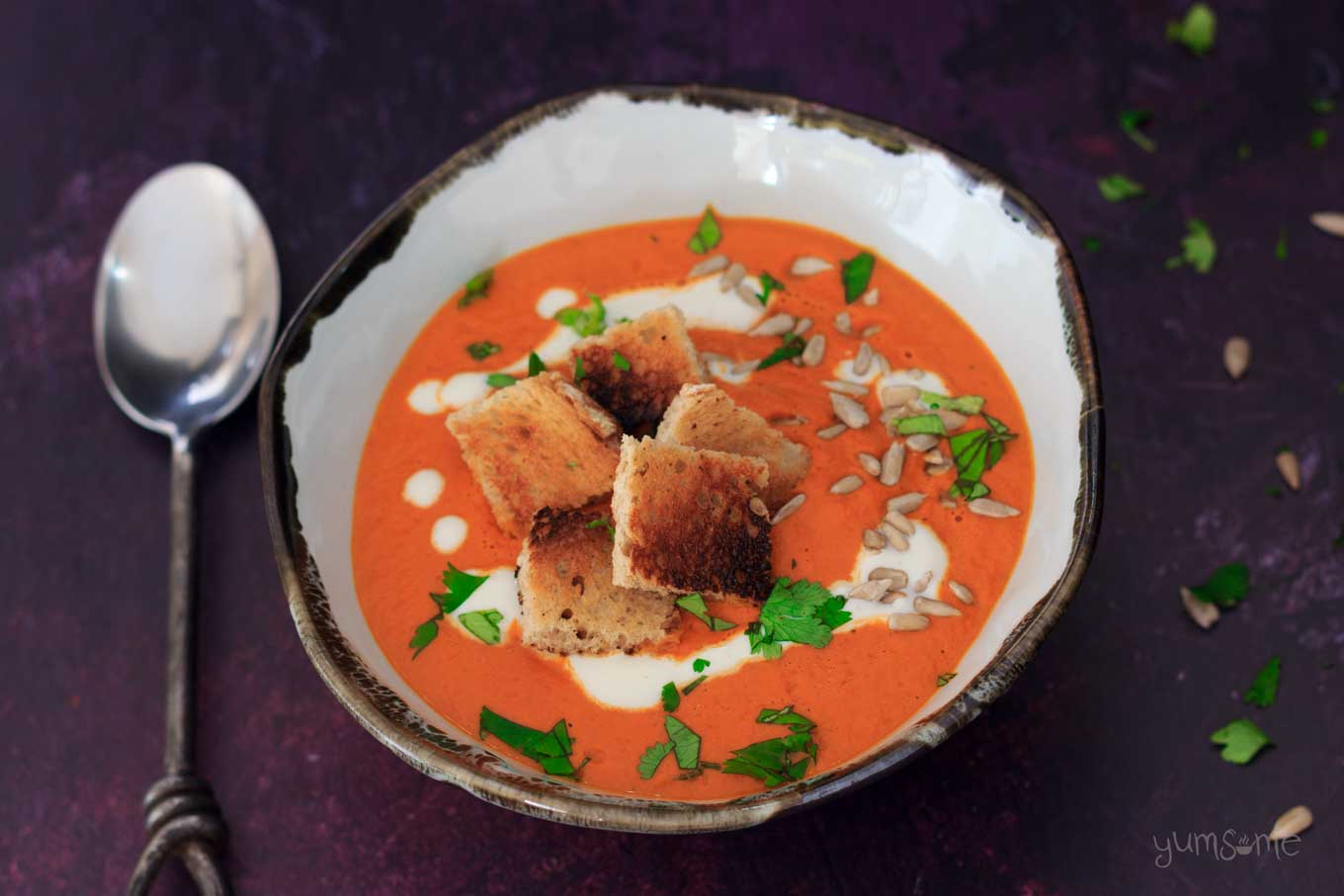 overhead image of a bowl of Creamy vegan tomato bisque with croutons | yumsome.com