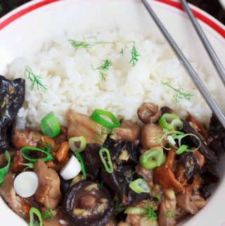 Asian-style mushrooms with ginger and rice in a white bowl, with silver chopsticks.